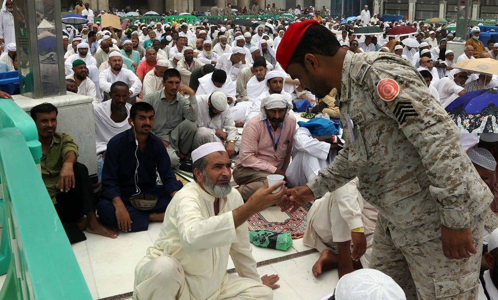 Saudische militair deelt water uit tijdens de Hadj